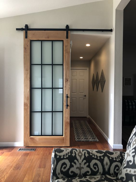 a stained barn sliding door done with frosted glass, with black frames is a cool solution for a rustic or farmhouse home