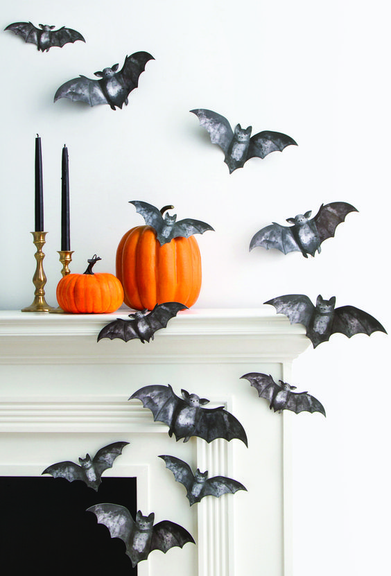 beautiful painted black paper bats attached to the wall and mantel, orange pumpkins and black candles in gold candlesticks
