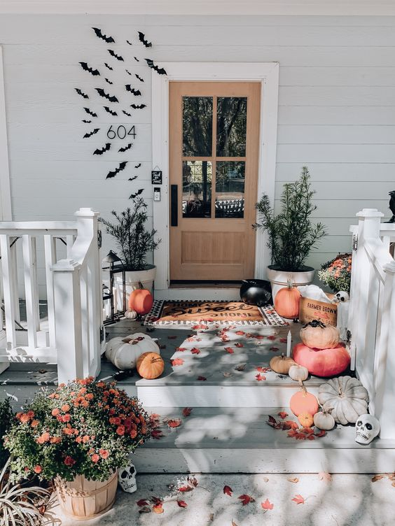 a beautiful Halloween front porch with natural pumpkins and skulls, potted greenery, black paper bats on the wall around the door