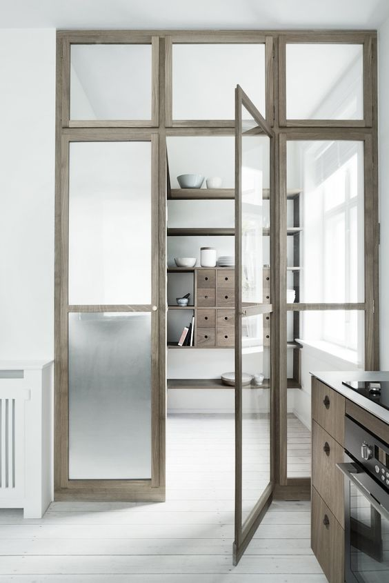 a large pantry divided from the kitchen with sheer and frosted glass doors ans windows lets the light from the window in the pantry go to the kitchen