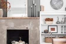 05 a modern farmhouse living room with a grey planked wall, a concrete fireplace with white and grey pumpkins plus other fall decor here and there