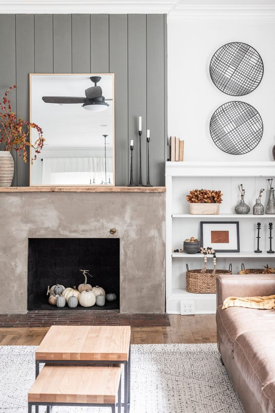 a modern farmhouse living room with a grey planked wall, a concrete fireplace with white and grey pumpkins plus other fall decor here and there