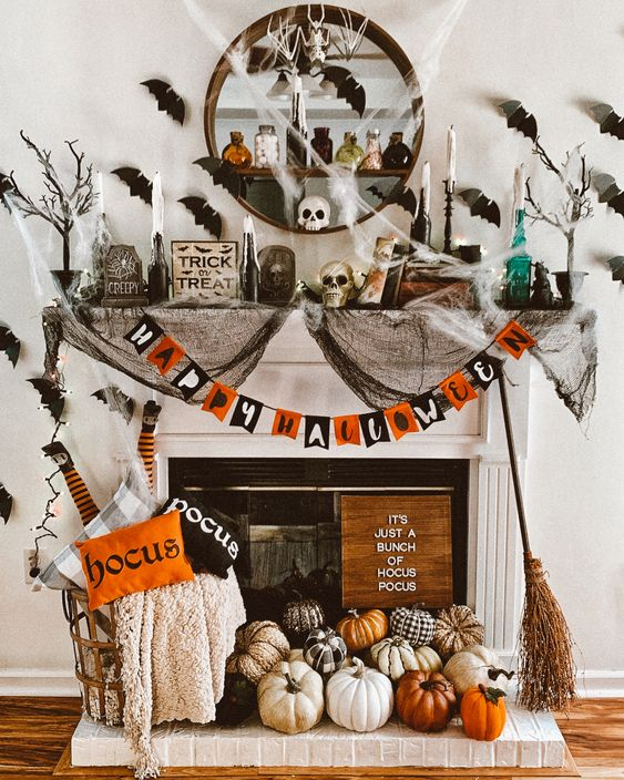 a colorful Halloween fireplace with a bold garland, lots of natural and faux pumpkins, printed pillows, black spider web, black bats on the wall