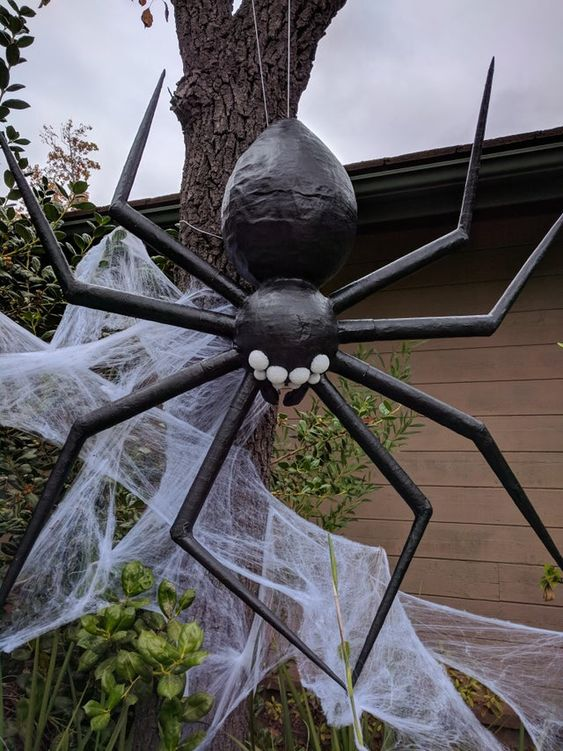 a giant black spider with realistic spiderweb is a stylish and scary idea to decorate your outdoor or even indoor space and it wows