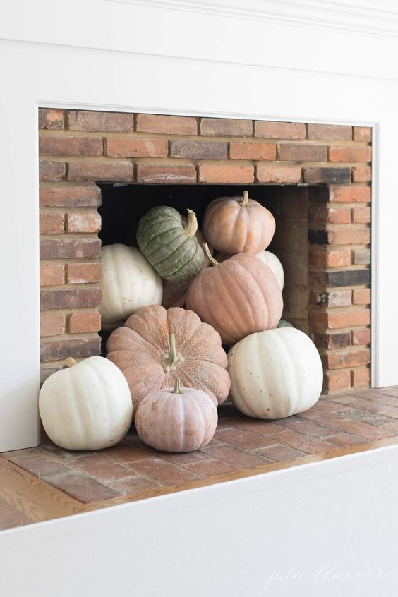 a modern fireplace with neutral and pastel pumpkins is a cool idea for a modern fall-embracing space and is an easy to realize decor idea