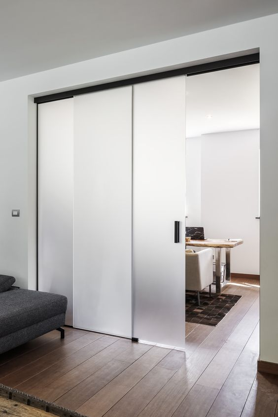 a modern home with delicate frosted glass sliding doors with black handles that separate the spaces in a sutble way without looking heavy