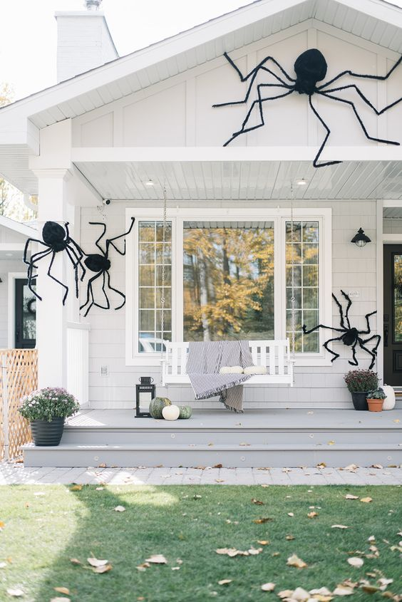 a house styled with giant black spiders looks scary and Halloween-like but still remains a farmhouse-style dwelling with an organic and natural feel