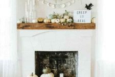 07 a modern fireplace with stacked pumpkins and pillar candles, with pumpkins and greenery on the mantel plus a sign