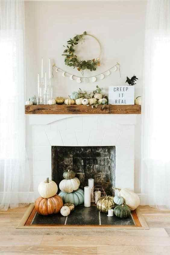 a modern fireplace with stacked pumpkins and pillar candles, with pumpkins and greenery on the mantel plus a sign