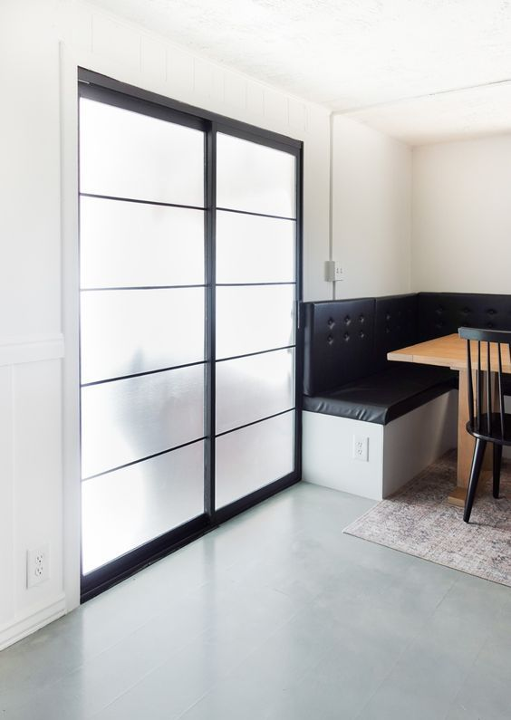 a sliding glass patio door with black frames is a great solution as it keeps privacy yet lets natural light inside and as it's sliding, it doesn't take any space