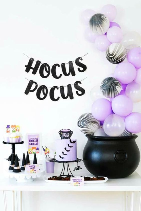 a black and lilac Halloween sweets table with a cauldron filled with lilac and marble balloons, a lilac cake with bats, sweets and a letter bunting