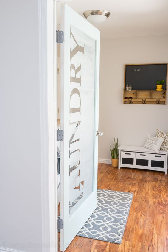 a frosted glass laundry door with letters is a cool and fresh idea to try for a modern farmhouse home