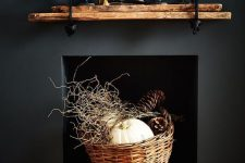 08 a modern rustic and woodland decoration – a black built-in fireplace with a basket with twigs, pumpkins and large pinecones is awesome for fall