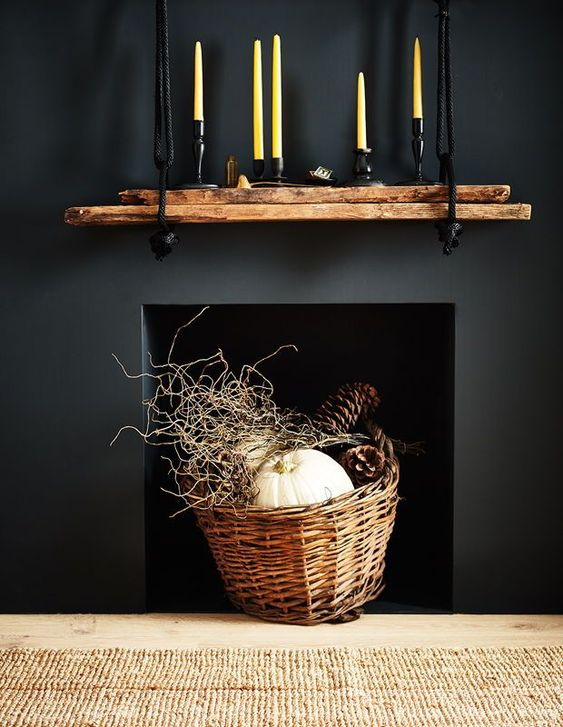 a modern rustic and woodland decoration   a black built in fireplace with a basket with twigs, pumpkins and large pinecones is awesome for fall