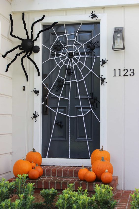 a stylish Halloween porch with pumpkins on the steps, a spiderweb and lots of black spiders of various sizes is very easy to recreate