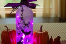 09 a bottle with purple lights and bats, with a purple bow on top and some pumpkins and leaves around for Halloween