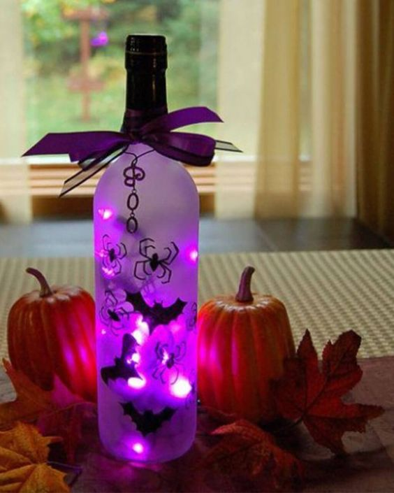 a bottle with purple lights and bats, with a purple bow on top and some pumpkins and leaves around for Halloween