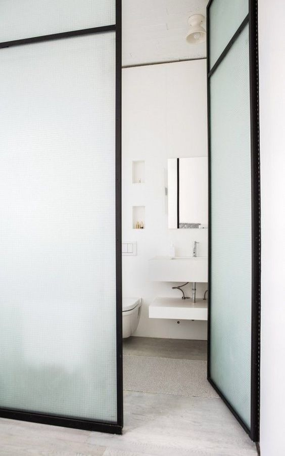 a neutral contemporary space with double-height frosted glass doors with black framing is a stylish idea to separate the spaces ina  delicate way and with style