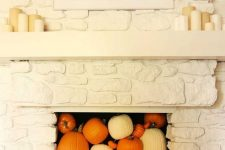 09 a white faux stone fireplace filled with white and orange pumpkins and gourds plus pillar candles on the mantel is a lovely idea