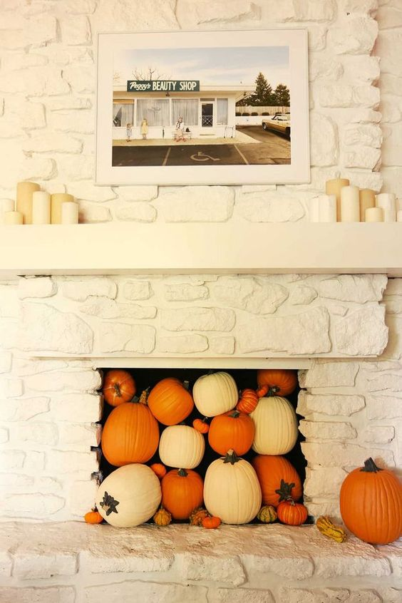 a white faux stone fireplace filled with white and orange pumpkins and gourds plus pillar candles on the mantel is a lovely idea