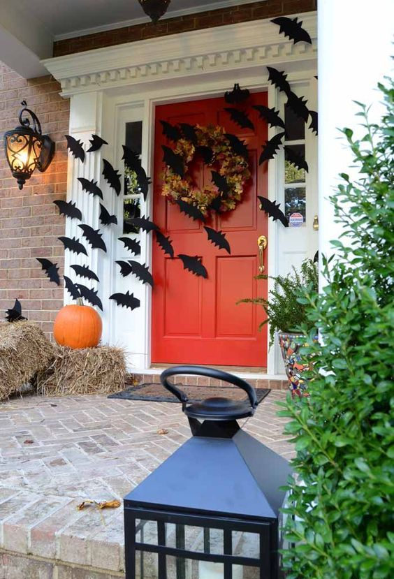 a Halloween and fall front porch with hay and an orange pumpkin, black bats attached to the walls and door, with a fall leaf wreath