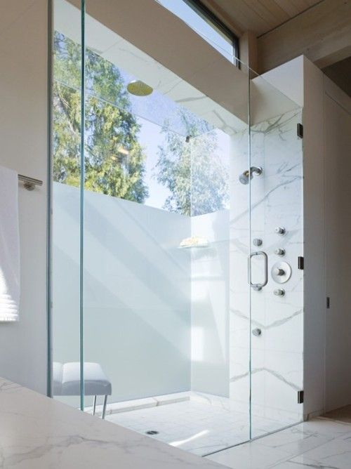 a contemporary neutral bathroom clad with white marble and with a glazed wall partly done with frosted glass for more intimacy
