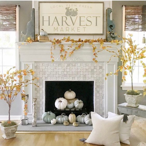 modern farmhouse fireplace styling with neutral and pastel pumpkins, potted plants around and some pumpkins on the mantel