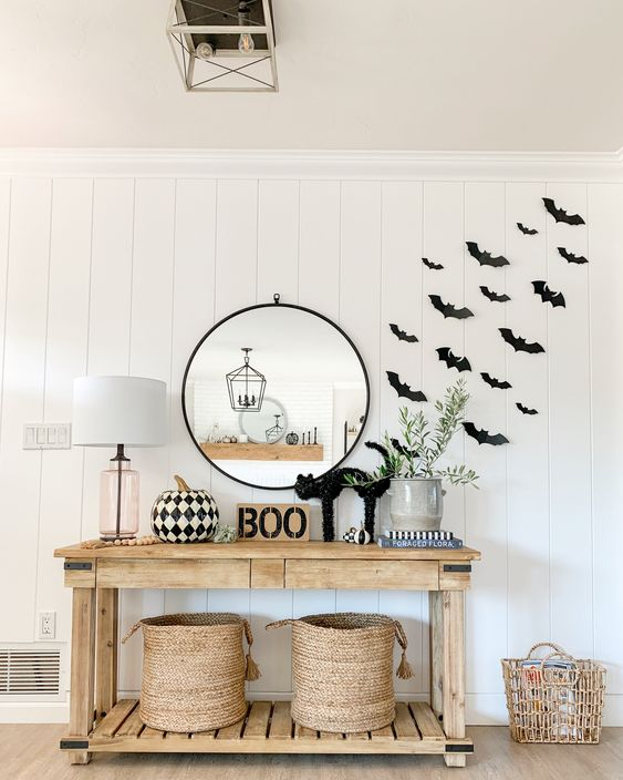a modern farmhouse space with black paper bats attached to the wall, a wooden console with a black cat, BOO, a black and white printed pumpkin