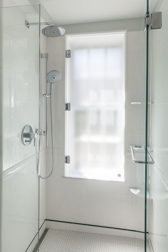 a sleek neutral shower space with a tall window covered with frosted glass, which is a smart and easy solution to go for