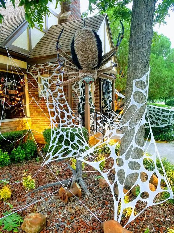faux spiderweb and an oversized and scary spider are amazing to style your outdoors or front porch for Halloween and are cool