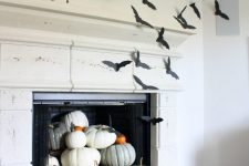 11 simple fireplace styling with heirloom pumpkins on stands is turned Halloween with simple black paper bats attached to the side