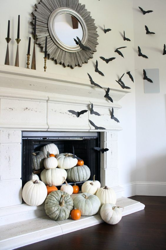 simple fireplace styling with heirloom pumpkins on stands is turned Halloween with simple black paper bats attached to the side
