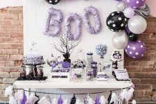 12 a black, white and purple Halloween sweets table with a ghost garland, lots of balloons and balloon letters