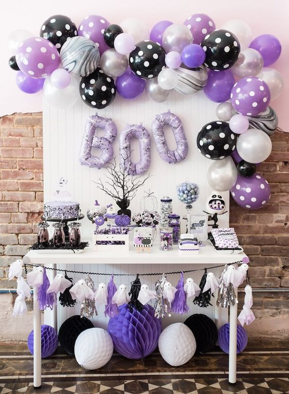 a black, white and purple Halloween sweets table with a ghost garland, lots of balloons and balloon letters