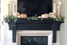 12 a built-in fireplace and white and pastel pumpkins in front of it plus some on the mantel with greenery and pillar candles