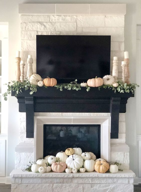 a built-in fireplace and white and pastel pumpkins in front of it plus some on the mantel with greenery and pillar candles