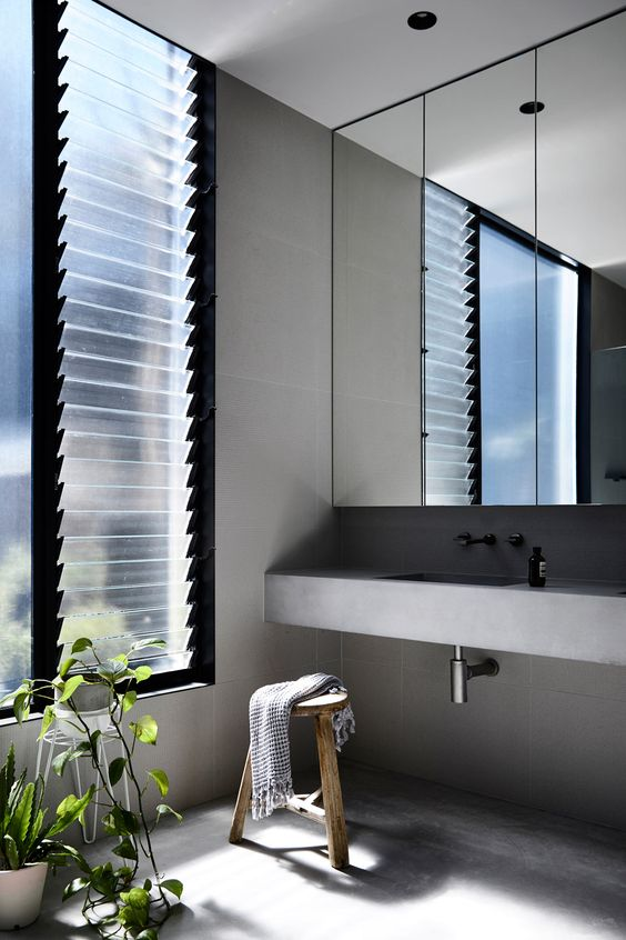 a minimalist bathroom of concrete, with a large window covered with frosted glass to keep privacy in the space and get natural light