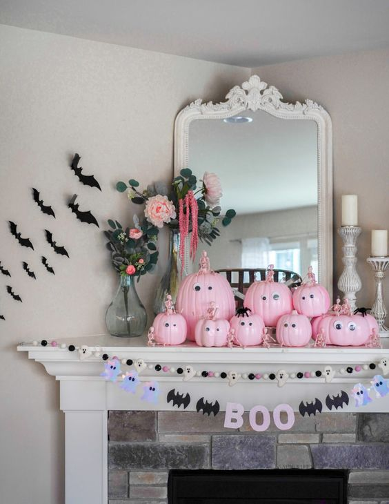 a pretty pastel Halloween mantel with bead and ghost and bat garlands, pink pumpkins with googly eyes and black bats on the wall
