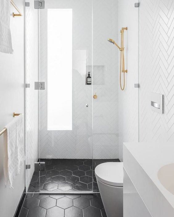 a small contemporary bathroom with white chevron tiles on the walls, black hex tiles, gold fixtures and a long and narrow window with frosted glass
