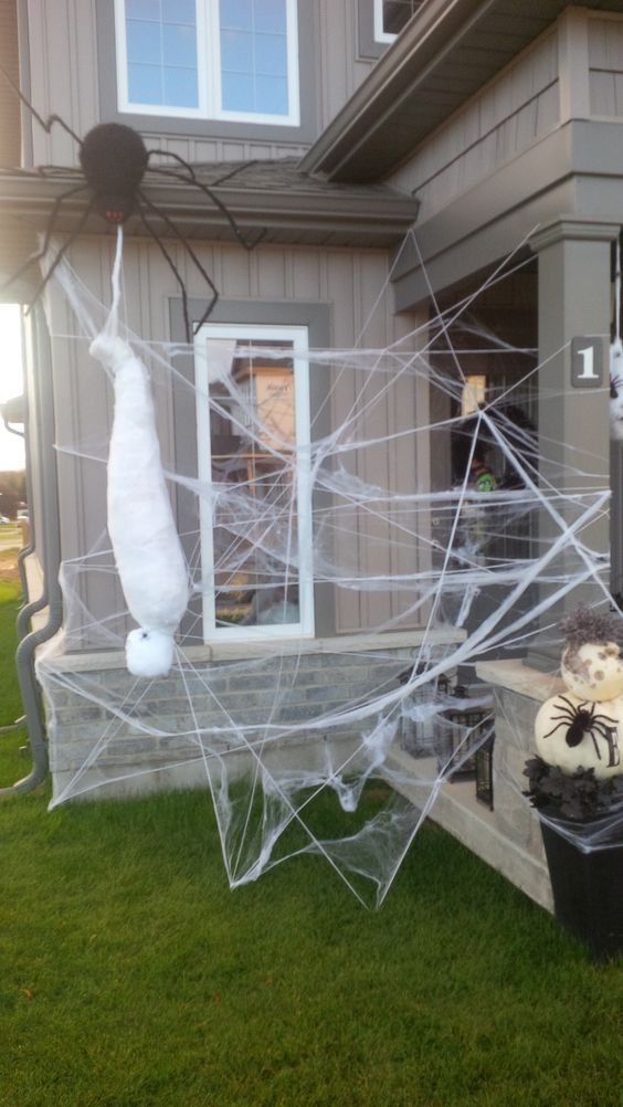 spiderwebs, a mummy, an oversized black spider and a small one on pumpkins is a cool idea to decorate a nook of your house or outdoors