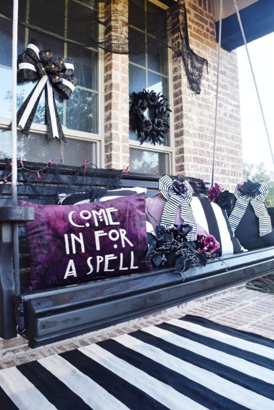 a black swing bench with black, white and purple pillows and faux purple blooms is a gorgeous idea for Halloween