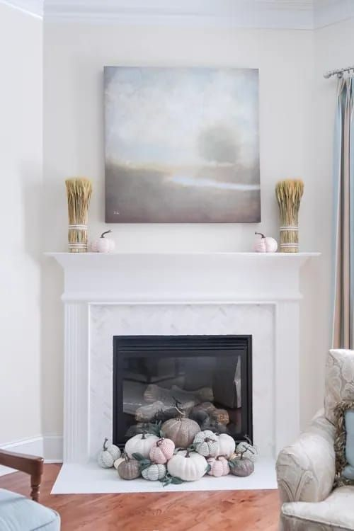 a built-in fireplace with pastel and neutral pumpkins in front of it, wheat and pumpkins on the mantel and a lovely artwork