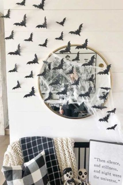 a round mirror covered with spider web and with black paper bats is a cool solution for a Halloween space