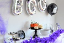 14 a black and white Halloween sweets table with purple and black balloons and a purple faux fur garland are amazing