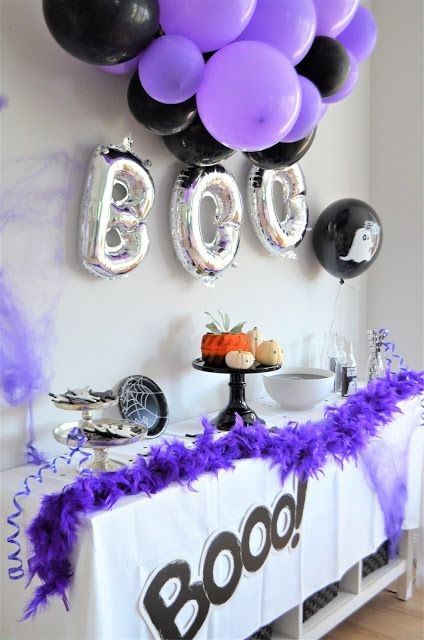 a black and white Halloween sweets table with purple and black balloons and a purple faux fur garland are amazing