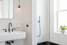14 a black and white bathroom with hex tiles on the floor, white stone walls, a large window with frosted glass for natural light