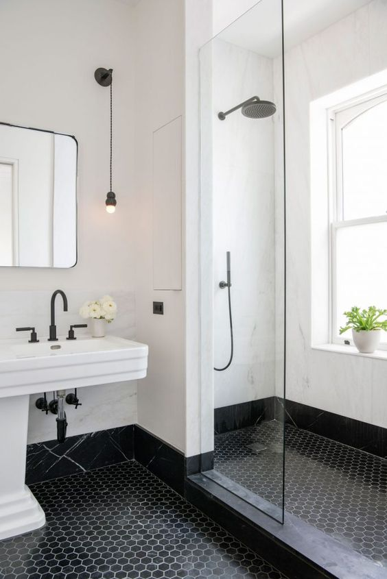 a black and white bathroom with hex tiles on the floor, white stone walls, a large window with frosted glass for natural light