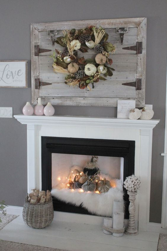 a fall fireplace styled with faux fur, fabric pumpkins and lights, a basket with firewood, candles and vases is a beautiful idea