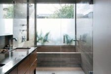 14 a modern warm-colored bathroom clad with wood-looking tiles and with a glazed wall that is done with frosted glass partly