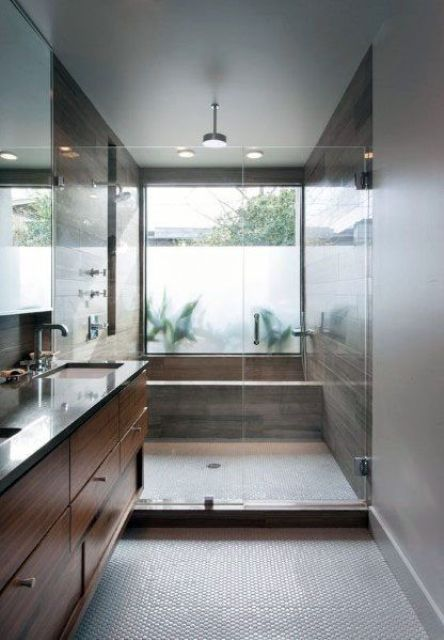 a modern warm-colored bathroom clad with wood-looking tiles and with a glazed wall that is done with frosted glass partly